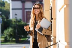 Photo of joyous woman holding laptop while walking through city street. Photo of joyous woman 20s holding laptop and drinking takeaway coffee while walking stock photo