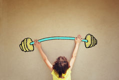 Photo of kid's back view lifting up barbell weights Stock Image