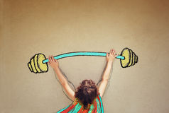 Photo of kid's back view lifting up barbell weights Royalty Free Stock Photos