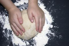 A kid`s hands, some flour, wheat dough and rolling pin on the black table with a place for text. Children hands making the rye do. A photo of kid`s hands, some stock photo