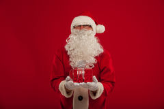 Photo of kind Santa Claus giving xmas present and looking at cam Royalty Free Stock Images