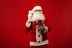 Photo of kind Santa Claus giving xmas present and Stock Photography