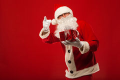 Photo of kind Santa Claus giving xmas present and Stock Images