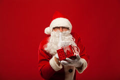 Photo of kind Santa Claus giving xmas present and Stock Photo