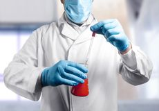 Laboratory assistant with flask. Photo of a lab assistant in outfit holding a flask and pipette Stock Photos