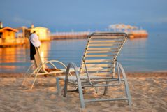 Photo of the lake with a pier and sunbeds on the beach August evening warm sun. stock image