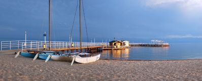Photo of the lake with a pier and sunbeds on the beach August evening warm sun. stock photo