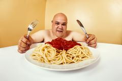 Hungry fat man eating spaghetti stock images