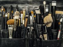 Bag of makeup brushes and apllicators. Photo of a leather bag filled with makup brushes and cosmetic applicators stock image