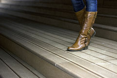 Photo of leather woman`s with boots on wooden trail. At night Stock Photos