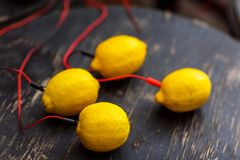 Photo of lemons with red wires on black wooden table royalty free stock photo