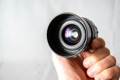 Photo lens from a SLR camera with beautiful colored glare on lenses. On a bright background stock image