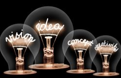 Light Bulbs Concept. Photo of light bulbs with shining fibres in IDEA, VISION, CONCEPT and CREATIVITY shape on black background Stock Photography