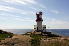 Photo of Lindesnes beacon in summer, South Norway. Aerial shot. Rocky sea coast and blue sky. Stock Photos