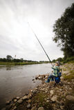 Photo of little boy fishing. On river coast Royalty Free Stock Image