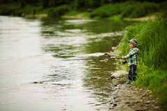 Photo of little boy fishing. On river coast Royalty Free Stock Photo