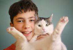 Photo of little funny boy hugs cat. Photo of cat lover teenager boy hug cat close up portrait Royalty Free Stock Photo