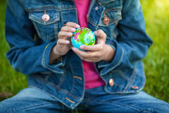 Photo of little girl holding globe and exploring it Royalty Free Stock Images