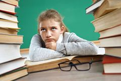 Photo of little girl lying on book in classroom royalty free stock photo