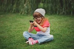 Little girl with mobile phone on the grass Royalty Free Stock Image