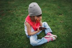 Little girl with mobile phone on the grass Royalty Free Stock Photography