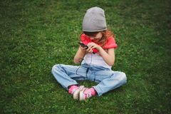 Little girl with mobile phone on the grass Stock Photography