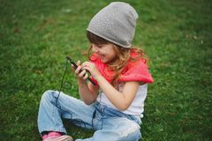 Little girl with mobile phone on the grass Stock Photo