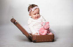 Photo of little girl sitting in old suitcase Stock Photography