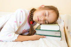 Photo of little girl sleeping in bed on pile of books Stock Image