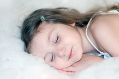 A photo of a little girl sleeping on a cotton wool cloud Royalty Free Stock Image