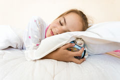 Photo of little girl sleeping and holding alarm clock under pill Stock Photo