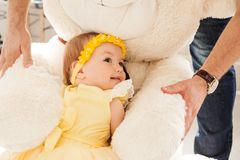 Little girl in a yellow dress hugs a big toy bear royalty free stock photo