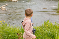 Photo of little kid pulling rod while fishing on weekend royalty free stock images