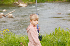 Photo of little kid pulling rod while fishing on weekend Stock Images