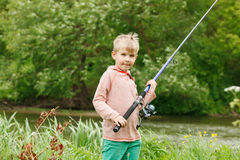 Photo of little kid pulling rod while fishing on weekend Royalty Free Stock Photo