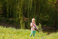 Photo of little kid pulling rod while fishing on weekend Stock Photography