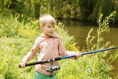 Photo of little kid pulling rod while fishing on weekend Stock Photo