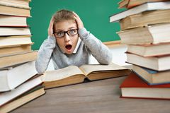 Photo of little schoolgirl with open mouth and big eyes around books. Student in shock. Photo of little schoolgirl with open mouth and big eyes around books Stock Images