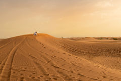 Photo of local resident praying on a dune of a desert in the Uni Stock Images