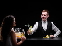 An attractive woman and bar worker smiling each other in a night club and on a black background. Copy space. Royalty Free Stock Photos