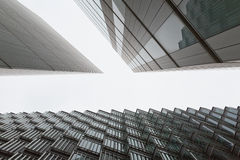 A photo looking up capturing three different buildings on an angle. Creating a horizontal white negative space between the buildings royalty free stock photos