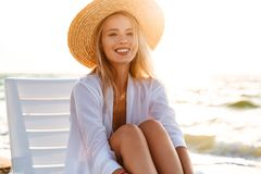 Photo of lovely european woman 20s in straw hat smiling, while s. Photo of lovely european woman 20s in straw hat smiling while sitting in deck chair at sea bank stock photography