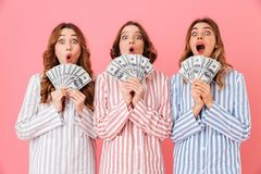 Photo of lovely teen girls 20s in colorful striped pyjamas holdi. Ng fans of money dollar bills and smiling on camera at slumber party isolated over pink Stock Photo