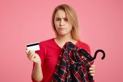 Photo of lovely woman with discontent expression goes shopping in fashionable boutique, chooses outfit, holds plastic card, has no Royalty Free Stock Images