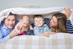 Photo of loving family  four lying on white bed in morning. Stock Photo