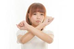 Photo lumineuse de la jeune femme asiatique faisant le geste d'arrêt Images stock