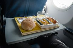 Photo of Lunch on board the aircraft. Photo of Lunch in the economy class on board the aircraft. Dish of Indian cuisine. Light snack on the background of the Royalty Free Stock Photo