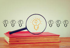 Photo of magnifying glass searching for a good idea light bulb. image is filtered Stock Photo