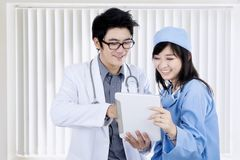 Medical staff using digital tablet together. Photo of male doctor and his partner using digital tablet while standing near the window in the hospital Royalty Free Stock Images