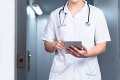 Bright photo of male doctor in uniform with stethoscope coming out of the elevator and using computer tablet in hospital stock images